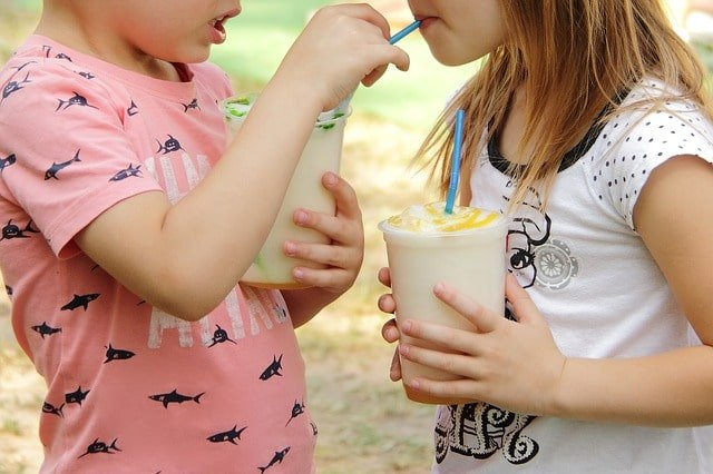 Two Kids Sharing Drinks